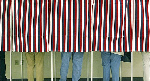 A photograph of occupied voting booths with curtains drawn